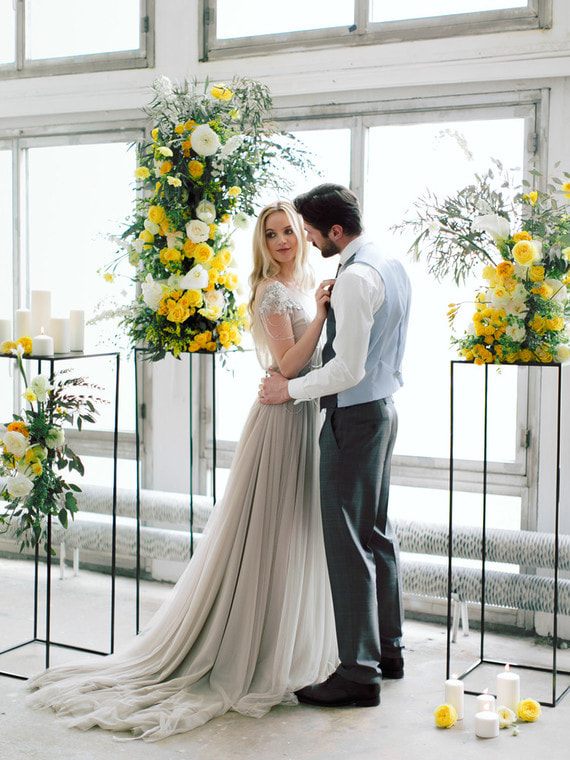 Gray chiffon bridal gown stands out against yellow floral decor in this muted venue.