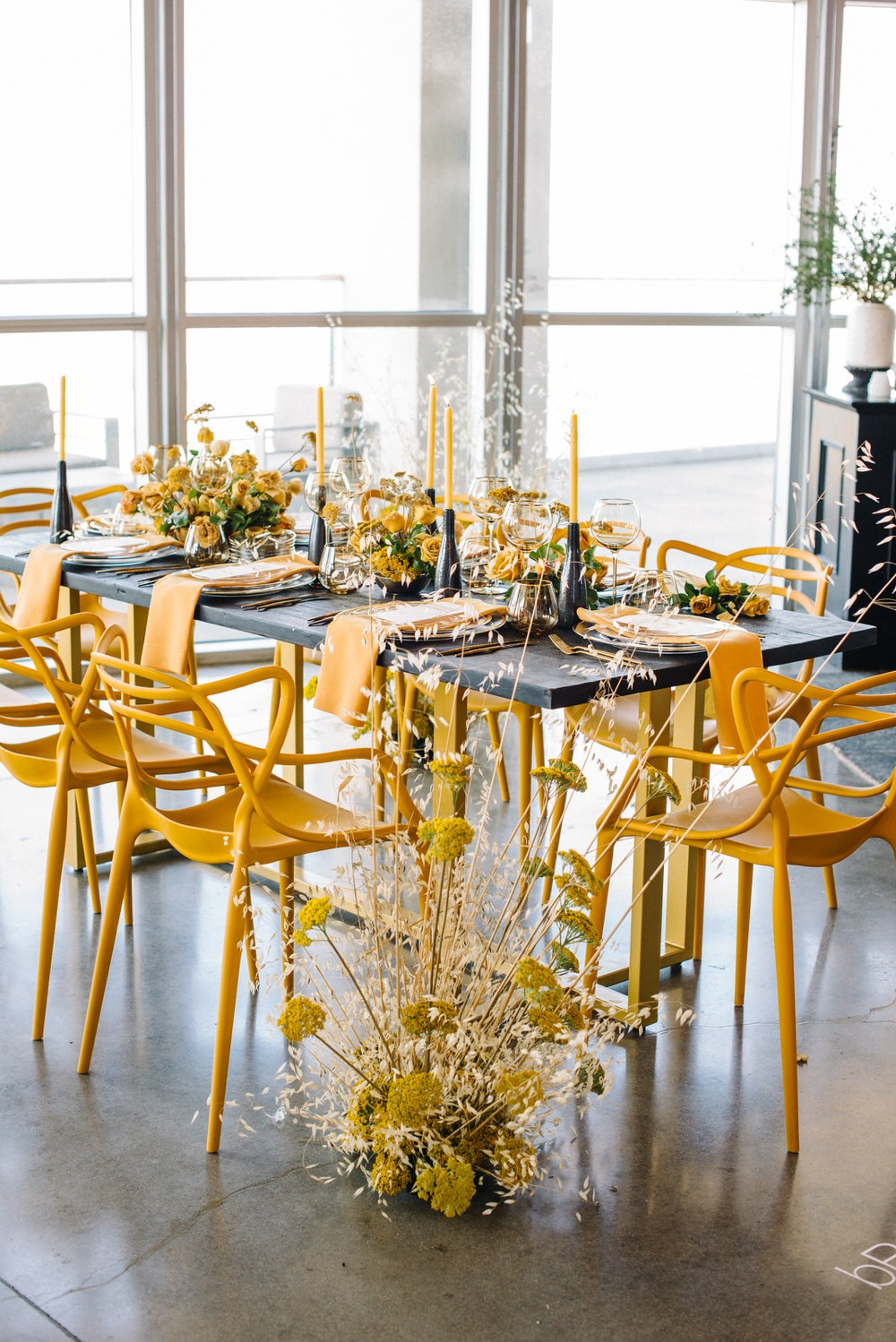 Architectural table design featuring yellow chairs and candles muted by black and gray table top decor.