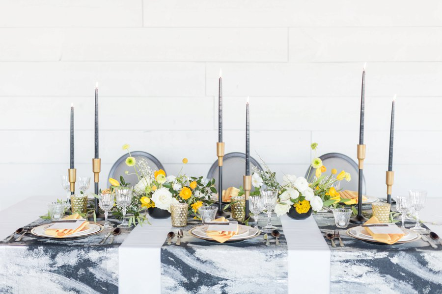 A gray marbled table top featuring gray accent decor softened with yellow florals.