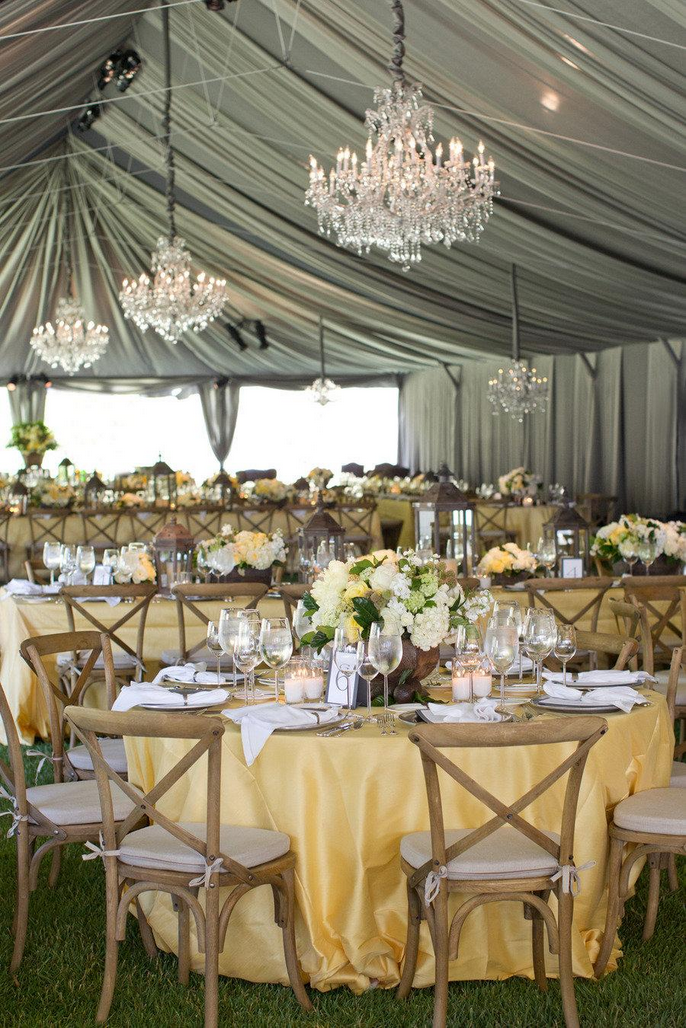 Grey chiffon tent liner with chandeliers and yellow table cloths.
